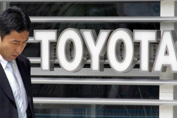 Seorang pria berjalan di depan showroom Toyota Motor Corp di Tokyo.